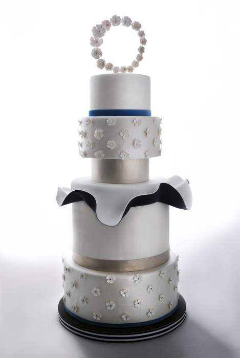 White Tiered Cake with Blue and Gold Accents and Flower Topper